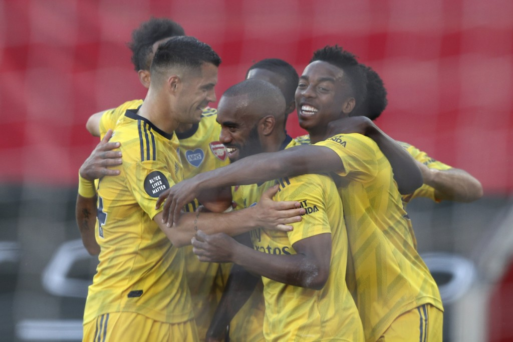 Arsenal's Joe Willock, right, celebrates with his teammates after scoring his side's second goal during the English Premier League soccer match betwee...