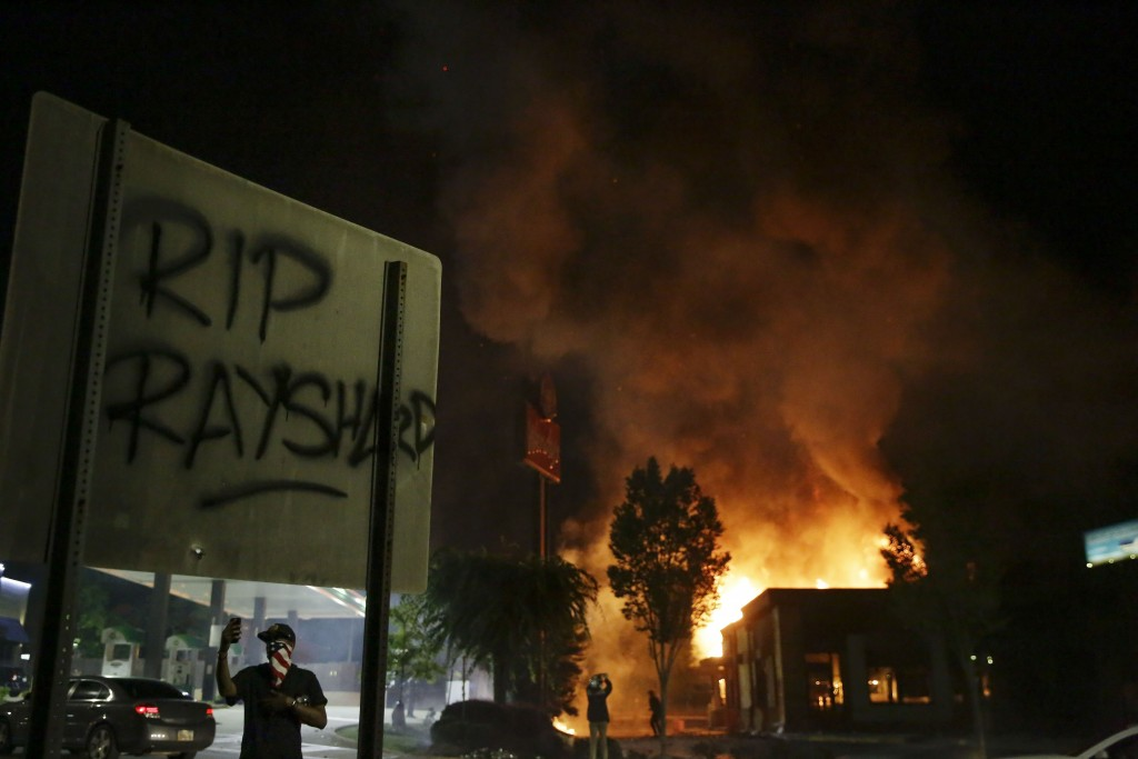 """File-In this Saturday, June 13, 2020 file photo, """"RIP Rayshard"""" is spray-painted on a sign as flames engulf a Wendy's restaurant where Rayshard Brooks..."""