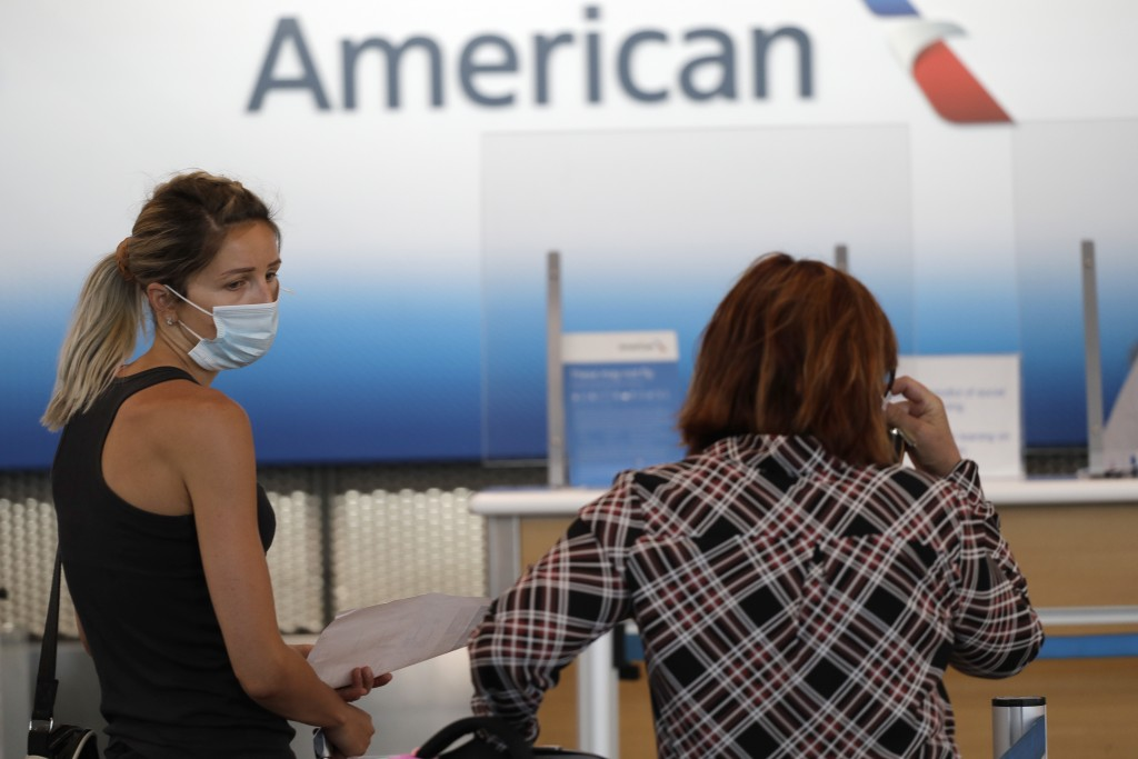 Travelers wear mask as they wait at the American Airlines ticket counter in Terminal 3 at O'Hare International Airport Tuesday, June 16, 2020, in Chic...