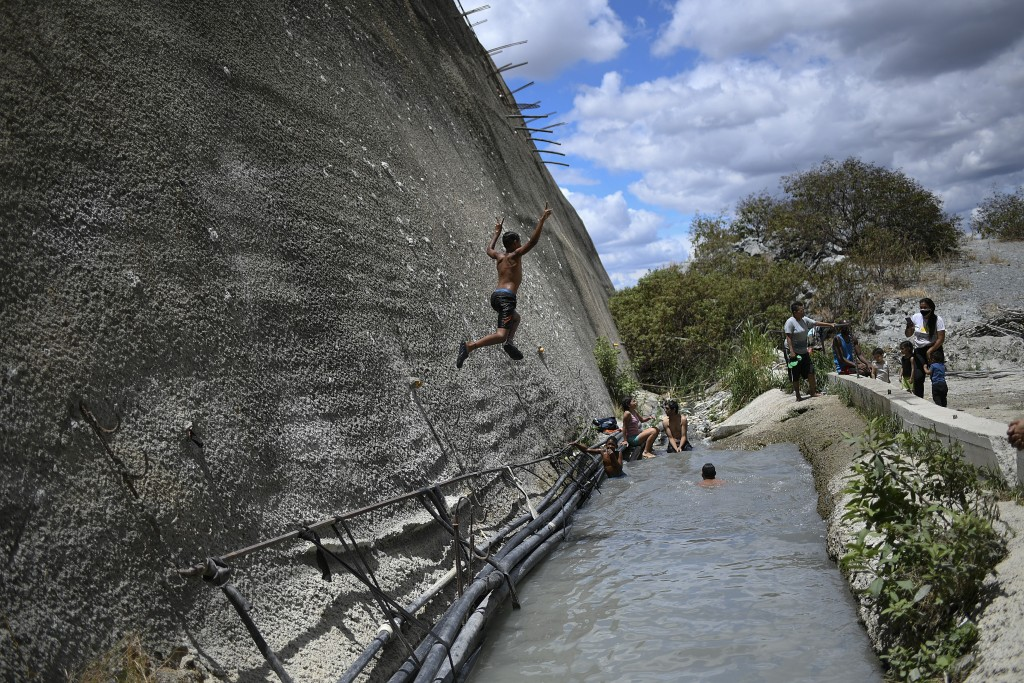 A boy jumps into a drainage ditch which channels water from an abandoned highway tunnel in Caracas, Venezuela, Saturday, June 6, 2020. Workers had lon...