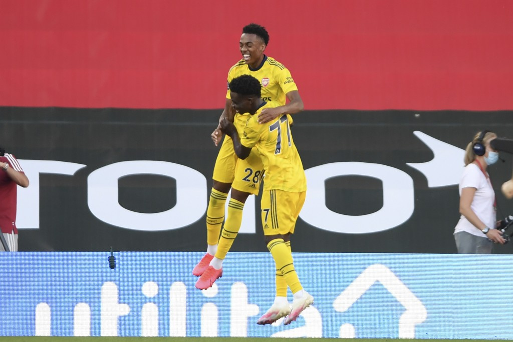 Arsenal's Joe Willock, top, celebrates with his teammate Arsenal's Bukayo Saka after scoring his side's second goal during the English Premier League ...