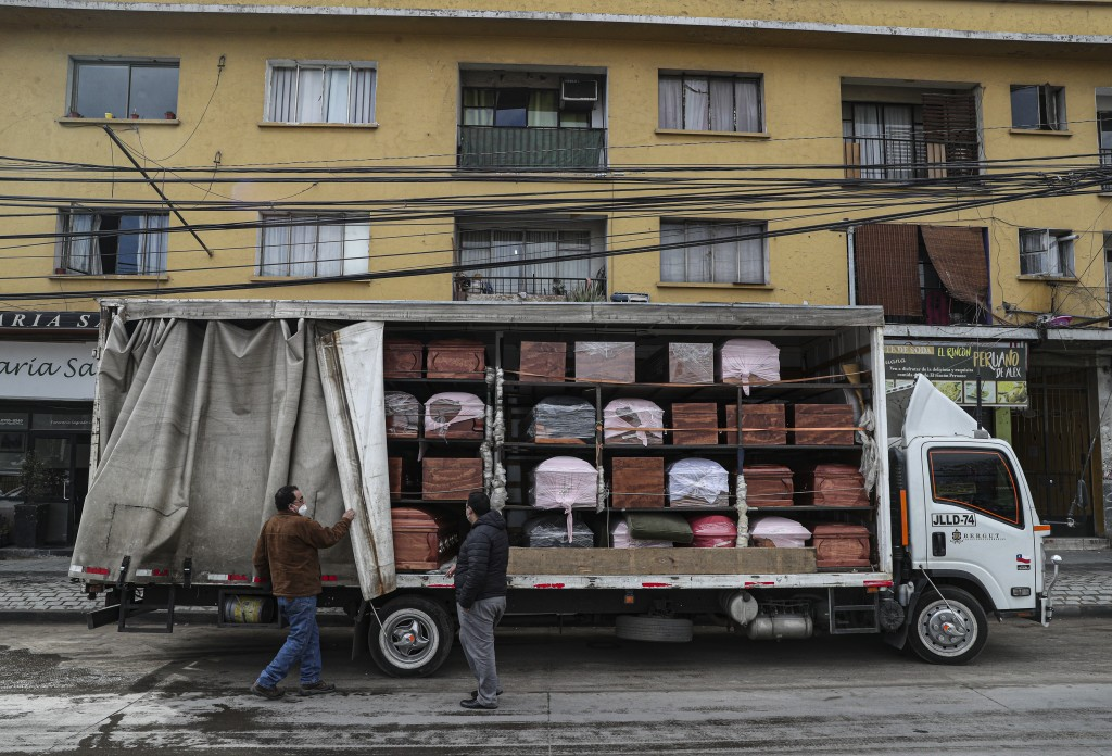 Bergut Funeral Services employees deliver coffins to a funeral store in Santiago, Chile, Friday, June 19, 2020. Coffin production has increased 120%, ...