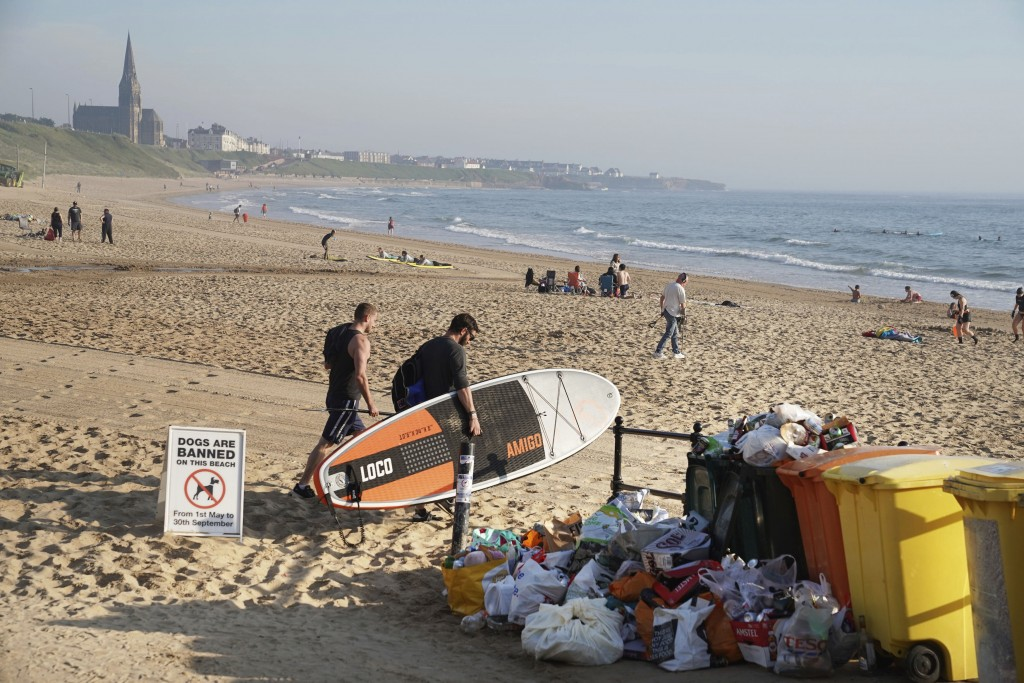 A man carrying a paddleboard passes rubbish collected by locals at Tynemouth beach after crowds gathered Thursday, in north east England, Friday June ...