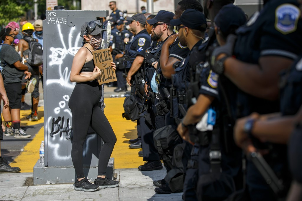 "FILE - In this June 23, 2020 file photo, A woman holds up a sign saying ""police the police"" as she confronts a police line while demonstrators protest..."