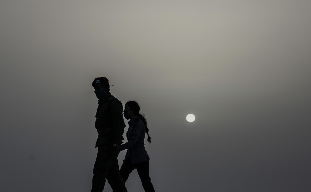 Police officers wearing masks as a precaution against the spread of the new coronavirus walk at dusk under a cloud of a Sahara dust hanging in the air...