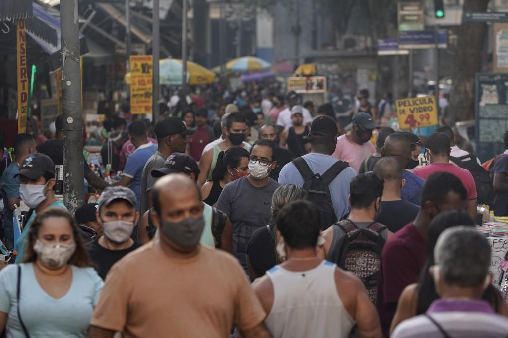 Pedestrians, some wearing protective face masks, walk through a street market in downtown Rio de Janeiro, Brazil, Thursday, June 25, 2020. With Latin ...