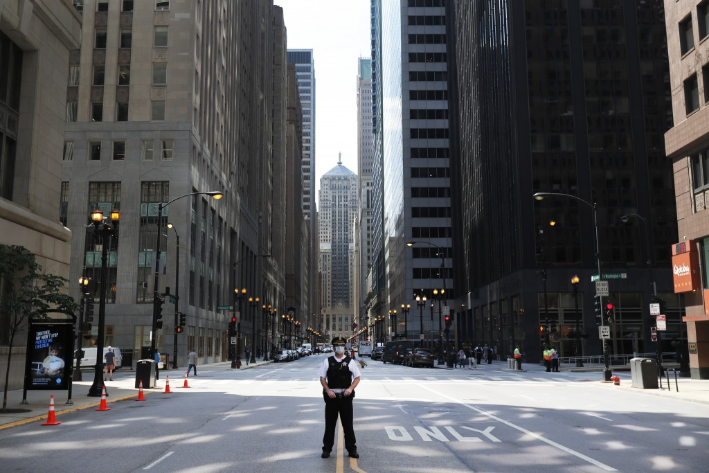 FILE - In this June 17, 2020, file photo a Chicago police officer stands alone on La Salle Street as he waits for protesters to continue their march c...