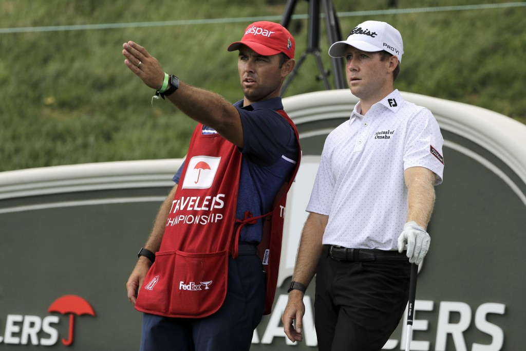 Tyler Duncan, right, talks to his caddie before teeing off on the 17th hole during the first round of the Travelers Championship golf tournament at TP...