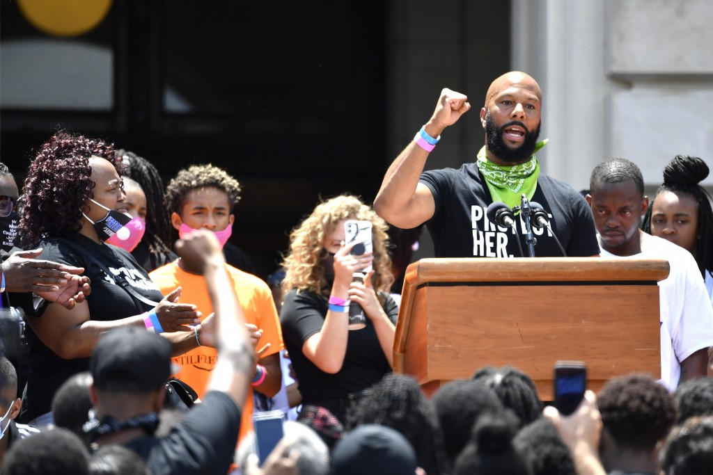 As Tamika Palmer, left, the mother of Breonna Taylor looks on, the artist Common addresses the crowd gathered on the steps of at the Kentucky State Ca...