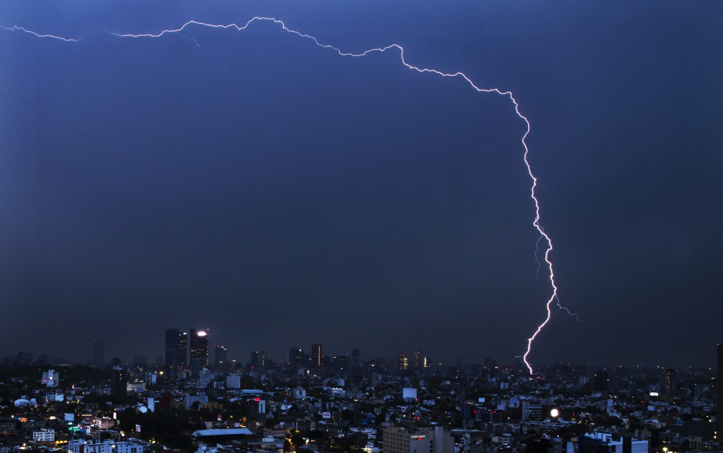 A bolt of lightning strikes during an early morning storm in Mexico City, Monday, June 22, 2020. (AP Photo/Marco Ugarte)