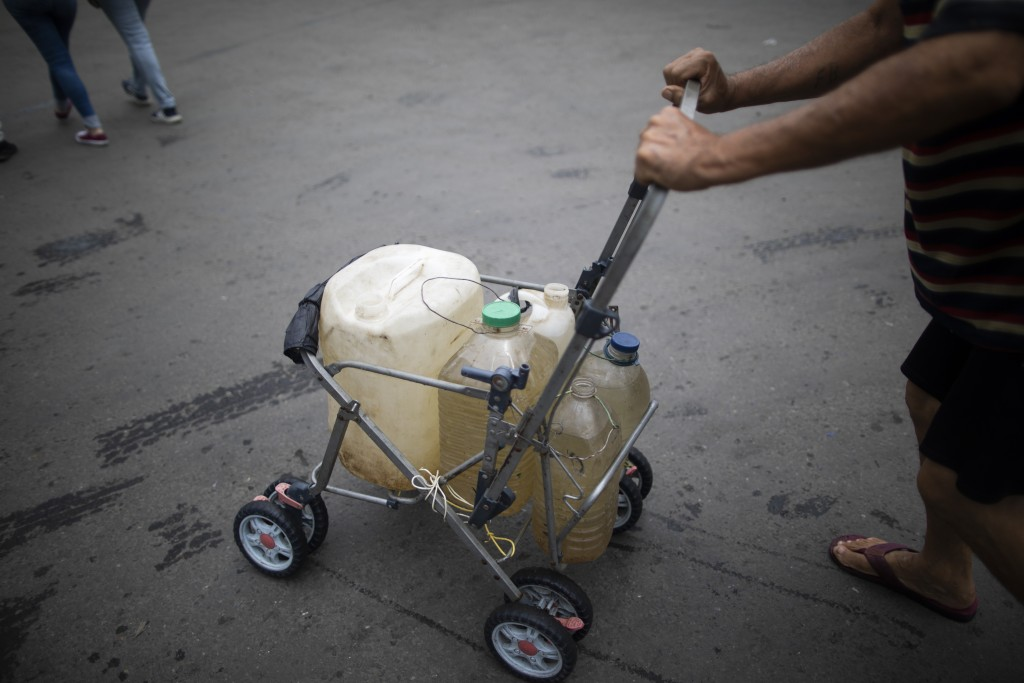 A man pushes a stripped down baby stroller with containers he filled with water that he collected from a street faucet, in Caracas, Venezuela, Saturda...