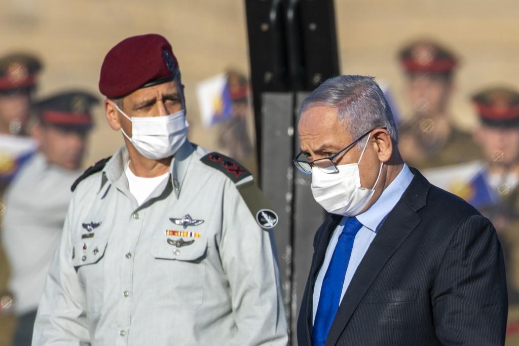 Israeli Prime Minister Benjamin Netanyahu, right, and Israeli Chief Aviv Kochavi, wearing face masks attend a graduation ceremony for new pilots in Ha...