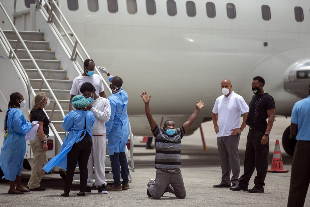 Roland Jean, a Haitian deported from the United States, kneels on the tarmac after arriving at the Toussaint Louverture airport in Port-au-Prince, Hai...