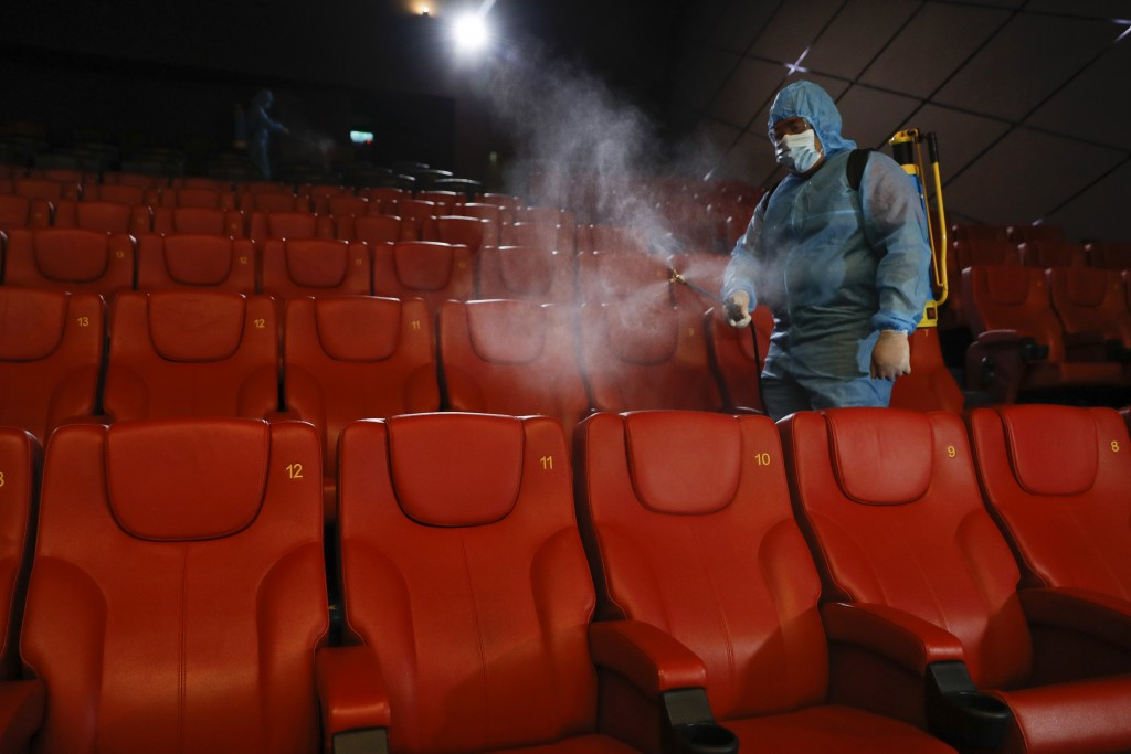 A staff member of a cinema sprays disinfectant at the cinema hall to prepare for reopening on July 1 in Kuala Lumpur, Malaysia, Friday, June 26, 2020....