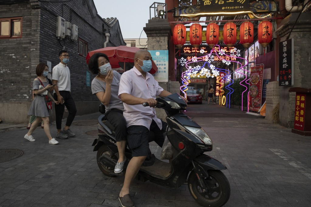 Residents wearing masks to curb the spread of the coronavirus past by lanterns and neon lights promoting a restaurant in Beijing on Friday, June 26, 2...