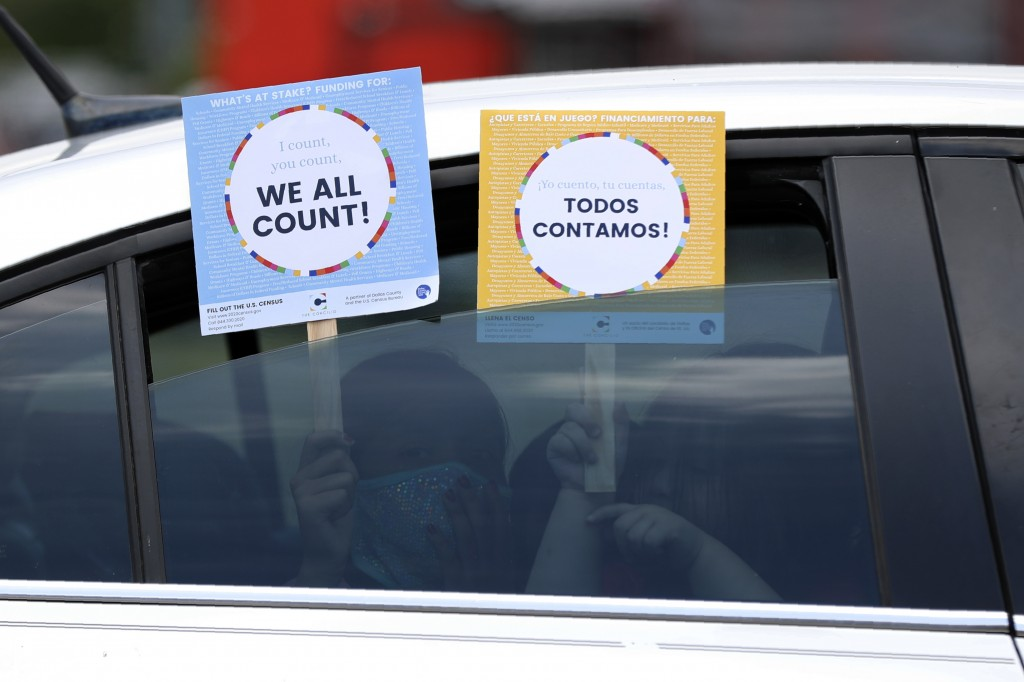 Two young children hold signs through the car window that make reference to the 2020 U.S. Census as they wait in the car with their family at an outre...