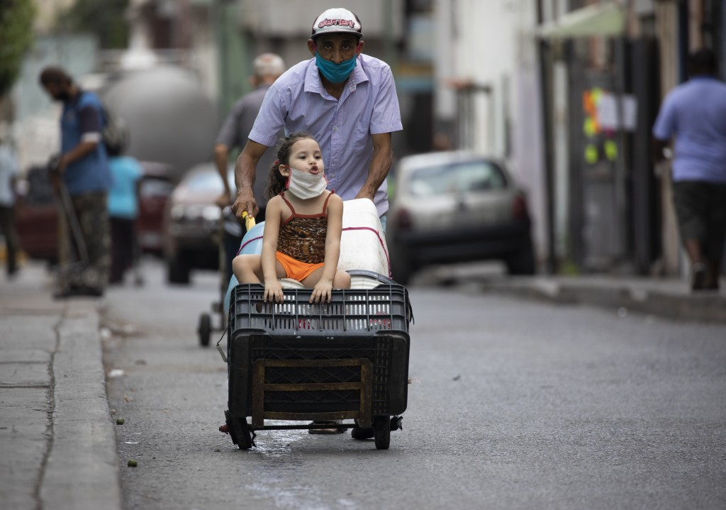 A man, wearing a protective face mask, pushes a dolly filled with empty containers, as he and a child go in search of water in Caracas, Venezuela, Sat...