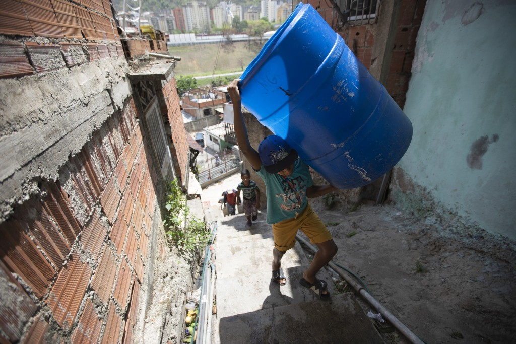 A child ascends a flight of stairs with an empty container to be filled with water provided by a government tanker truck in the Petare neighborhood of...