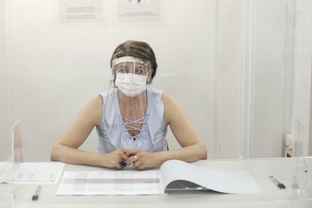 A woman wearing a face mask and visor to protect against coronavirus sits behind a glass shield during a rehearsal of the vote for the local elections...