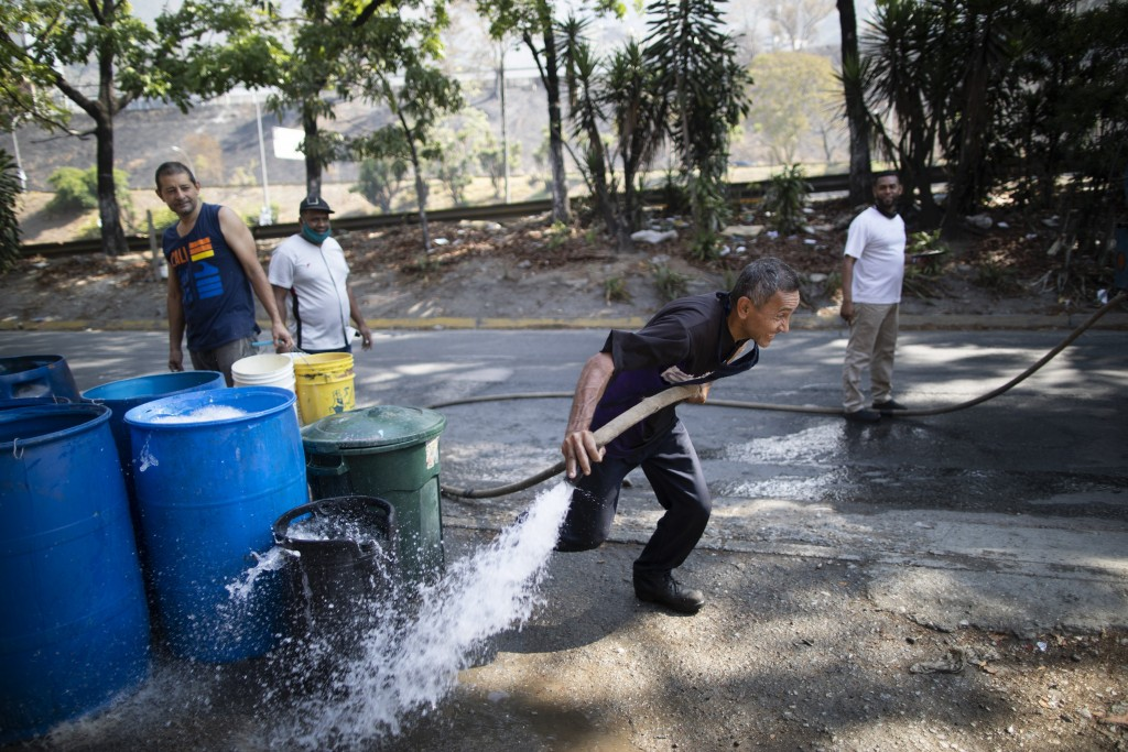 A worker controls a water hose from a government tanker truck to distribute water to residents in the Petare neighborhood of Caracas, Venezuela, Thurs...