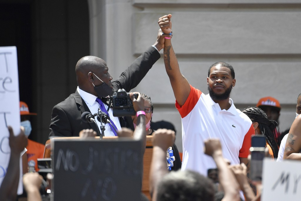Attorney Benjamin Crump, left, holds up the hand of Kenneth Walker during a rally on the steps of the Kentucky State Capitol in Frankfort, Ky., Thursd...