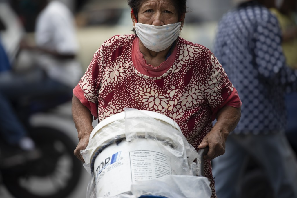 A woman, wearing a protective face mask, pushes a dolly of containers filled with water, in Caracas, Venezuela, Saturday, June 20, 2020. An estimated ...