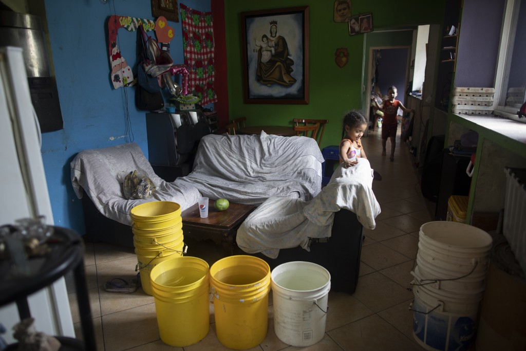 Buckets, some of them filled with water provided by a government tanker truck, are stored in the living room of a house in the Petare neighborhood of ...