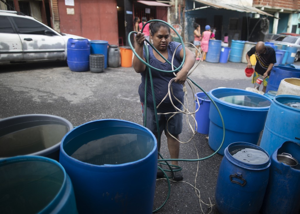 A woman untangles an electrical cord and a hose in order to pump from a large container water provided by a government tanker truck, in the Petare slu...