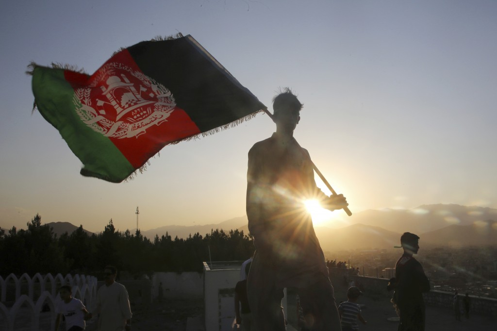 FILE - In this Aug. 19, 2019, file photo, a man waves an Afghan national flag during Independence Day celebrations in Kabul, Afghanistan. Washington's...