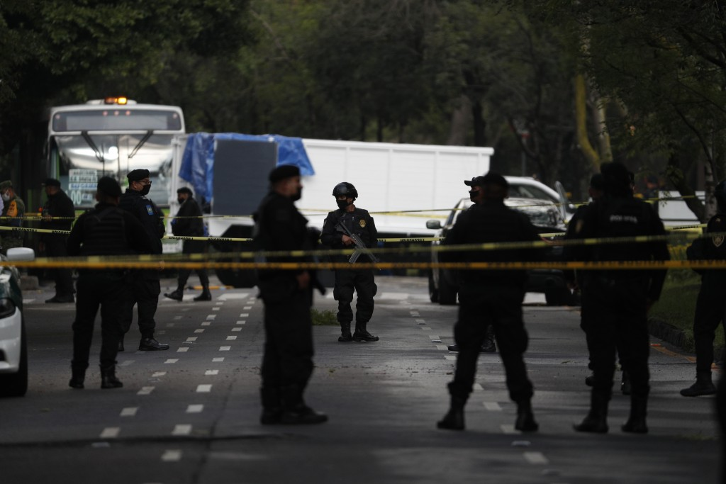 Police stand guard at a crime scene where the chief of police was attacked by gunmen in the early morning hours, in Mexico City, Friday, June 26, 2020...