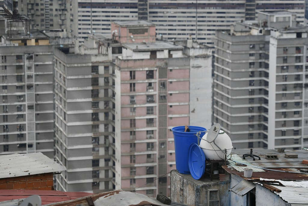 A man cleans the inside of a water container situated on the roof of his home in the San Agustin neighborhood of Caracas, Venezuela, Sunday, May 17, 2...