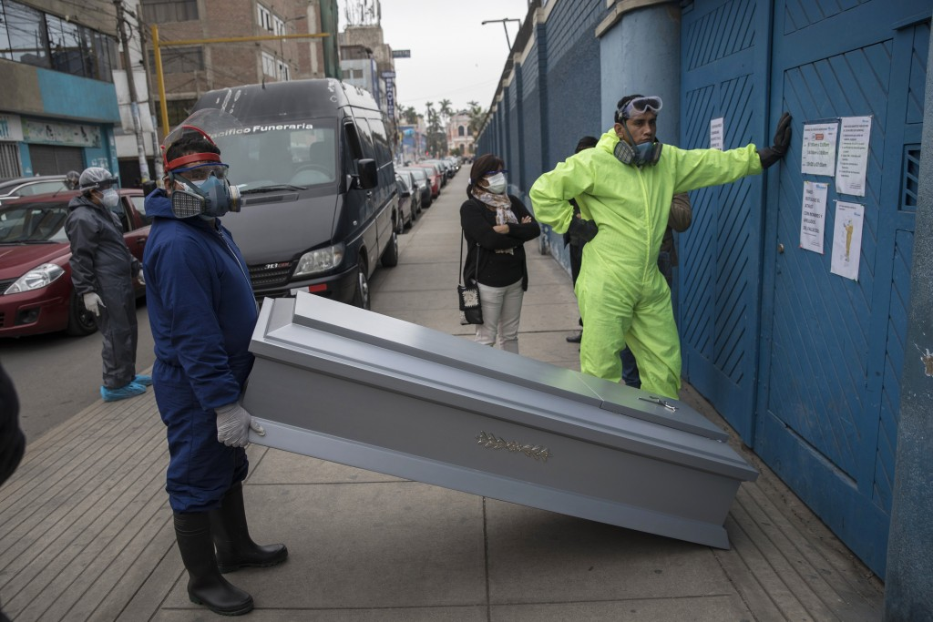 Funeral home workers wait their turn to pick up a body of a client who died from COVID-19, outside Almenara public hospital in Lima, Peru, Thursday, J...