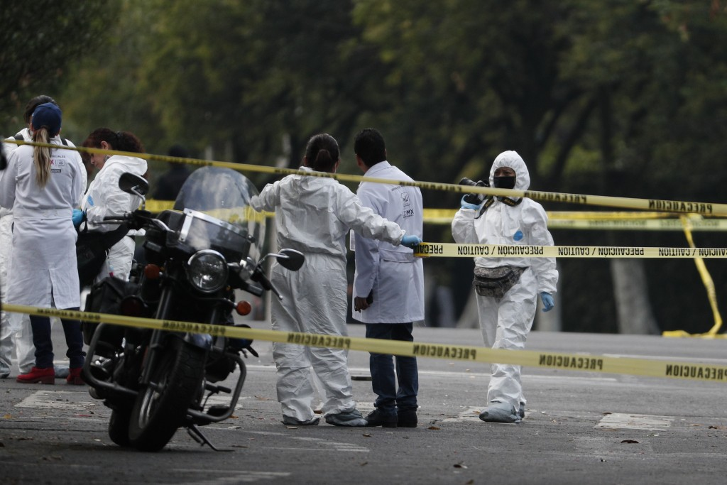 Forensic investigators and police work the scene where security secretary, Omar García Harfuch, was attacked by gunmen in the early morning hours in M...