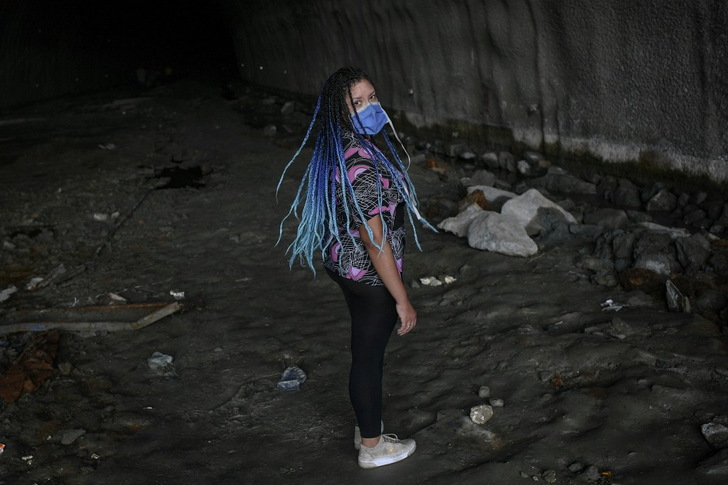 A woman wearing a protective face mask, turns around as she is called by a friend, in the Baralt highway tunnel in Caracas, Venezuela, Sunday, June 7,...