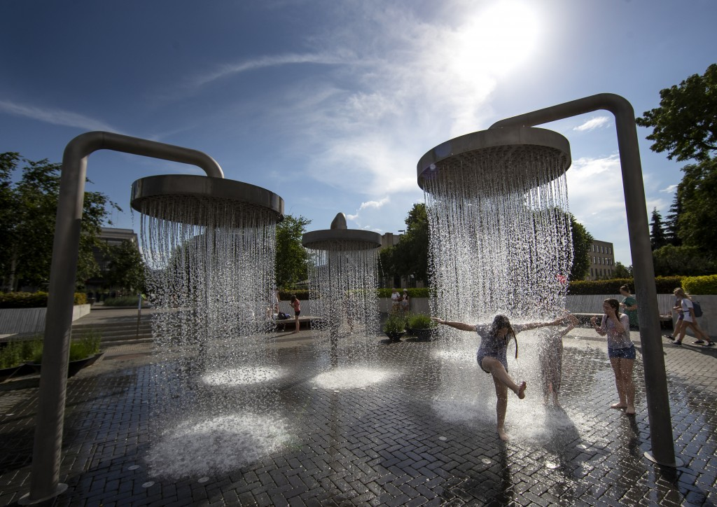 Children cool off in a public fountain in Vilnius, Lithuania, Friday, June 19, 2020. Heat wave continues in the Lithuania as temperature goes up high ...