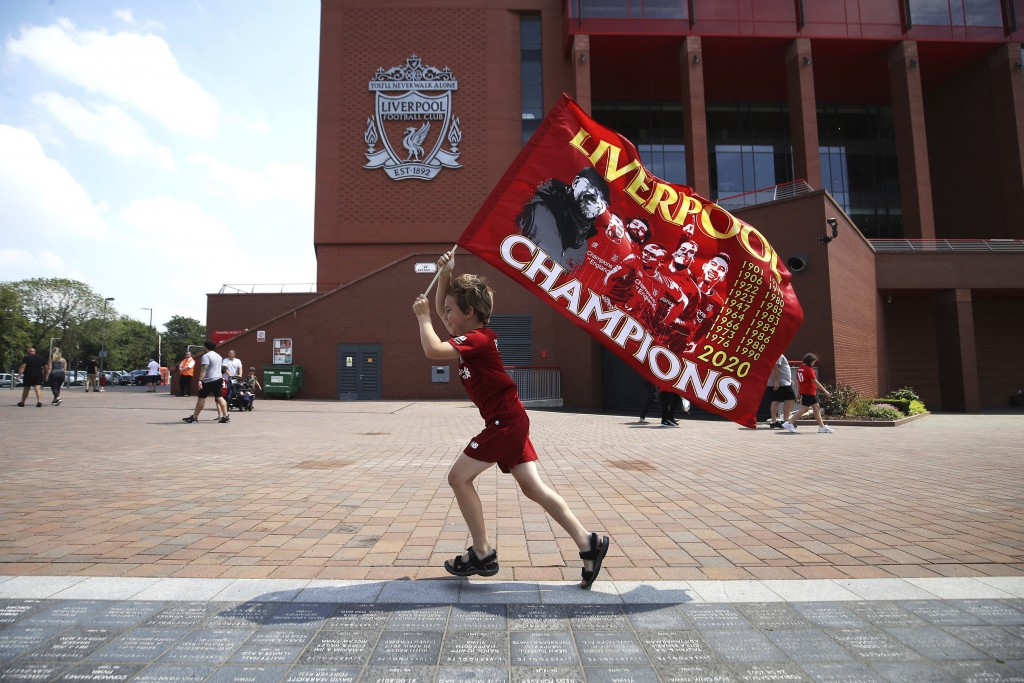 Liverpool fan Dillon Parry waves a flag outside Anfield in Liverpool, England, Friday June 26, 2020. Liverpool clinched its first league title since 1...