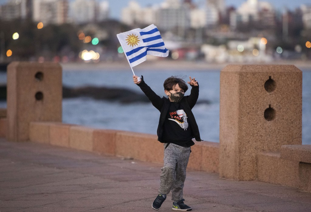 A boy wearing a protective face mask as a measure to curb the spread of the new coronavirus, waves a Uruguayan national flag as he plays on the seafro...