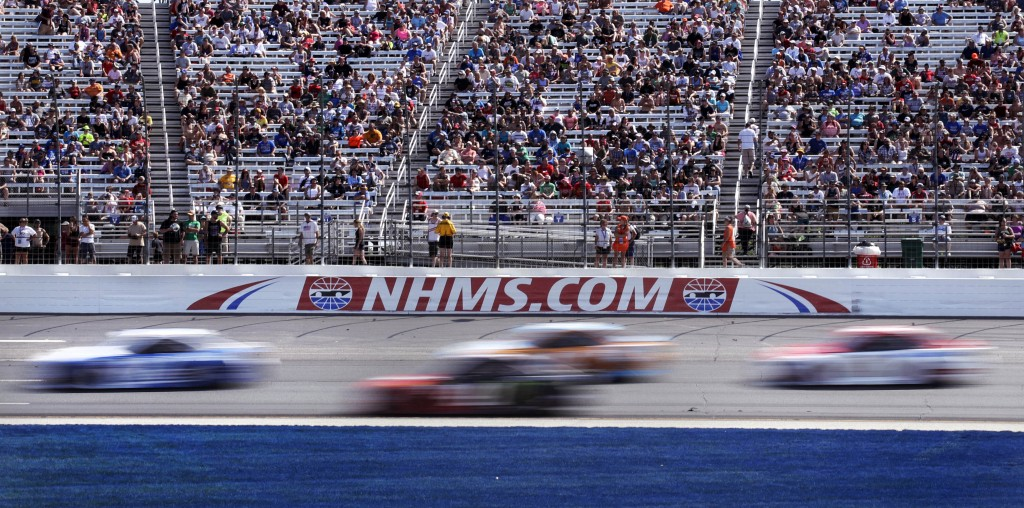 FILE - In this July 16, 2017, file photo, cars steer through Turn 1 as fans watch from nearly half-full stands during the NASCAR Cup Series 301 auto r...