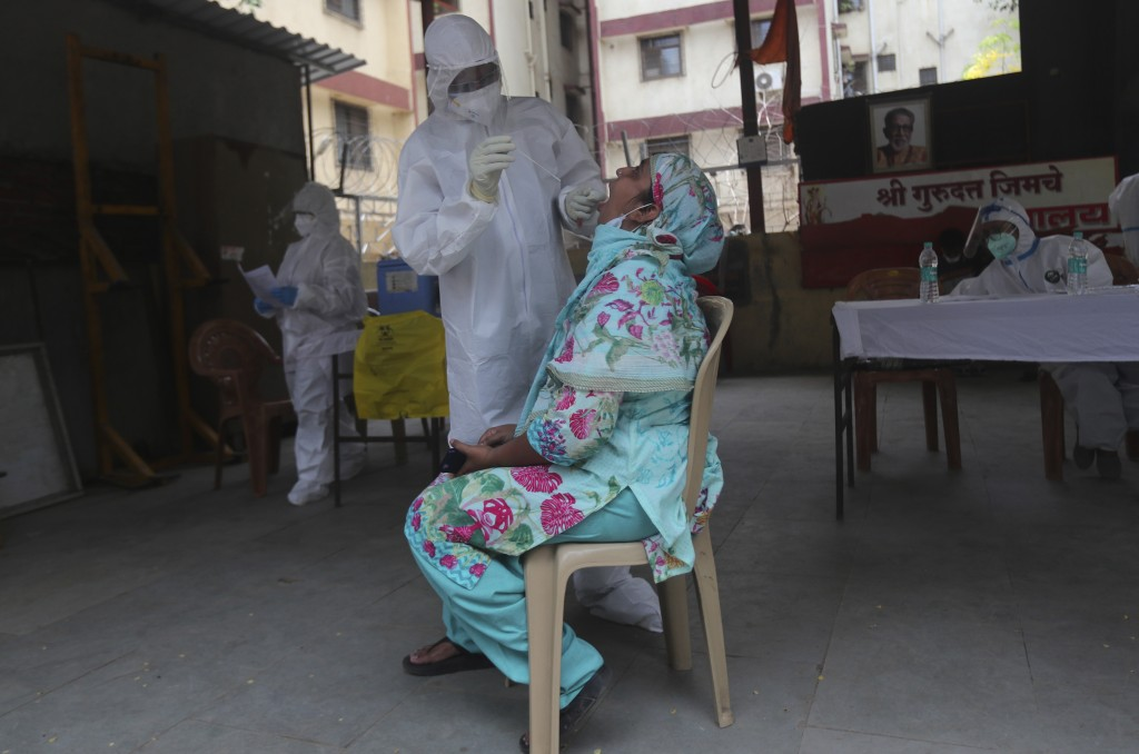 A health worker takes a swab test of a woman during a free medical checkup in Dharavi, one of Asia's biggest slums, in Mumbai, India, Friday, June 26,...