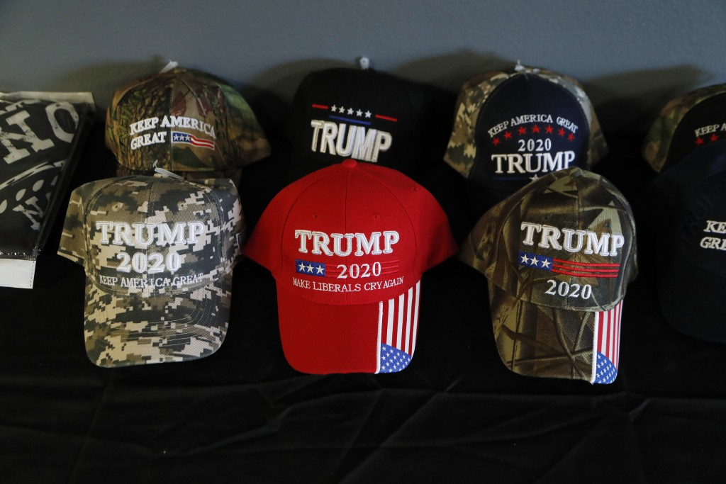 FILE - In this Jan. 8, 2020, file photo, a display of President Trump baseball caps at the Bedford Trump Train headquarters in Temperance, Mich. The c...