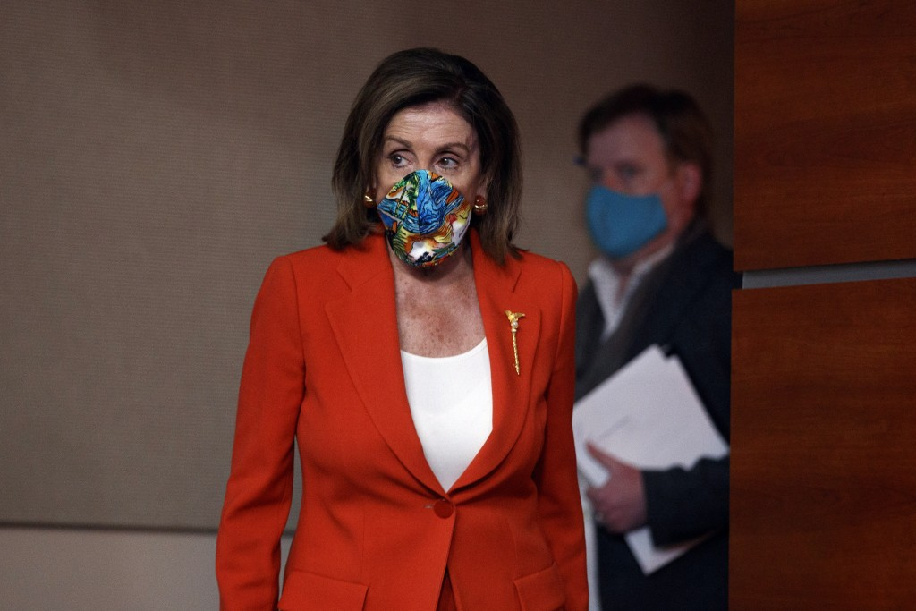 House Speaker Nancy Pelosi of Calif., wears a face mask as she arrives to speak at a news conference on Capitol Hill in Washington, Friday, June 26, 2...