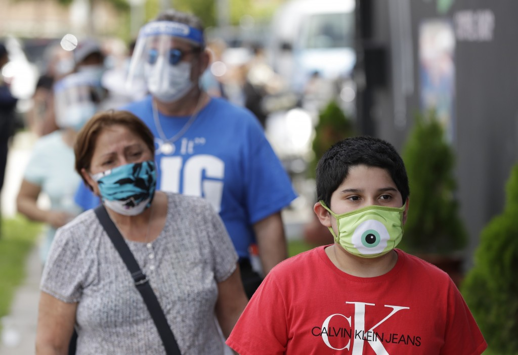 People, social distancing and wearing masks to prevent the spread of the new coronavirus, wait in line at a mask distribution event, Friday, June 26, ...