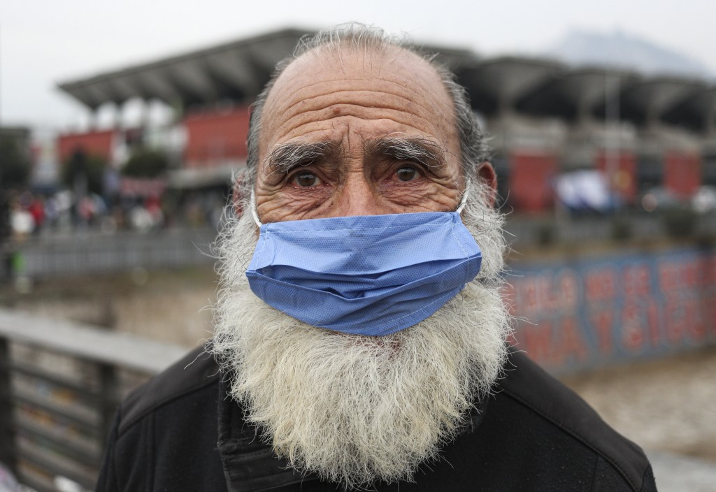 A man wearing a protective face mask as a precaution amid the new coronavirus pandemic, poses for a photo after buying groceries at a market in Santia...