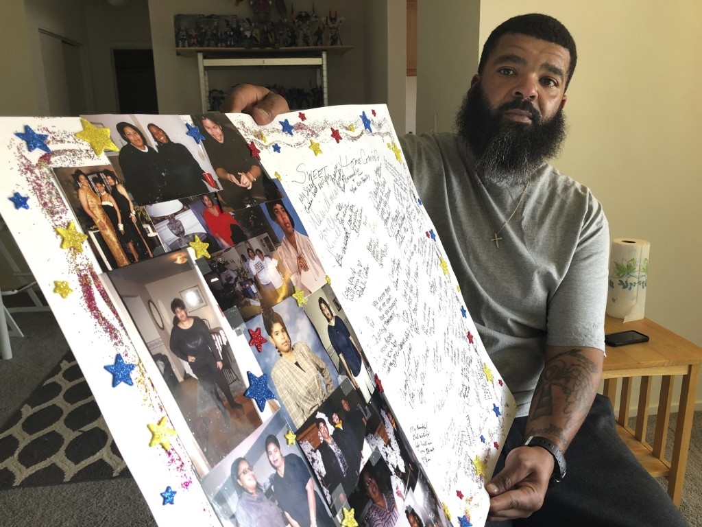 Roland Mack holds a poster with pictures and messages made by family members in memory of his sister, Chantee Mack, in District Heights, Md., on Frida...