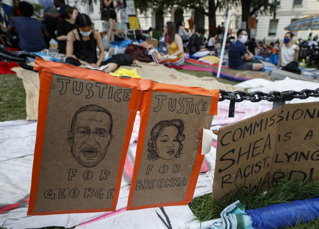 Protesters rest on a grassy area at an encampment outside City Hall, Friday, June 26, 2020, in New York while surrounded by signs calling for justice ...