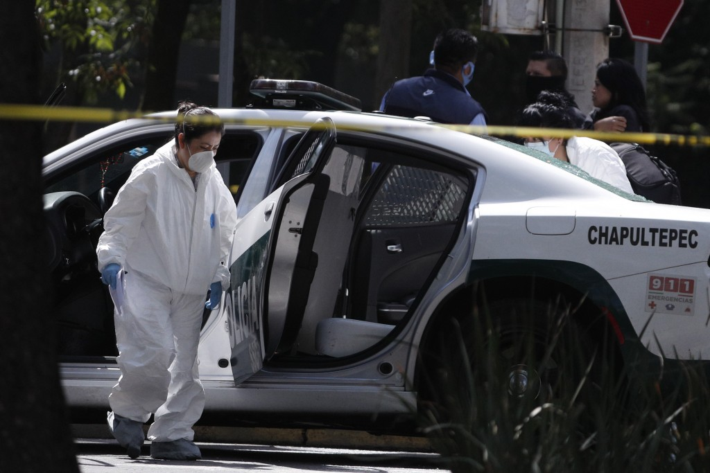 A forensic investigator inspects a police vehicle at the scene where the Mexican capital's police chief was attacked by gunmen in Mexico City, Friday,...