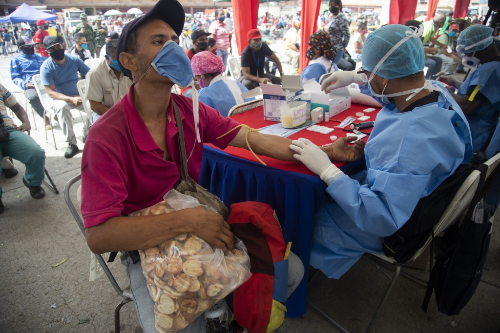 A health worker takes a blood sample for a quick COVID-19 test from man who works selling cookies at the Coche food market in Caracas, Venezuela, Tues...