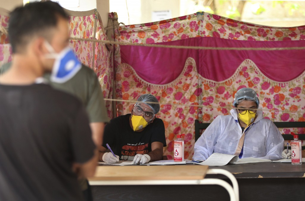 An Indian doctor interacts with a man as another waits for his turn at COVID-19 screening facility inside a government run hospital in Jammu, Saturday...