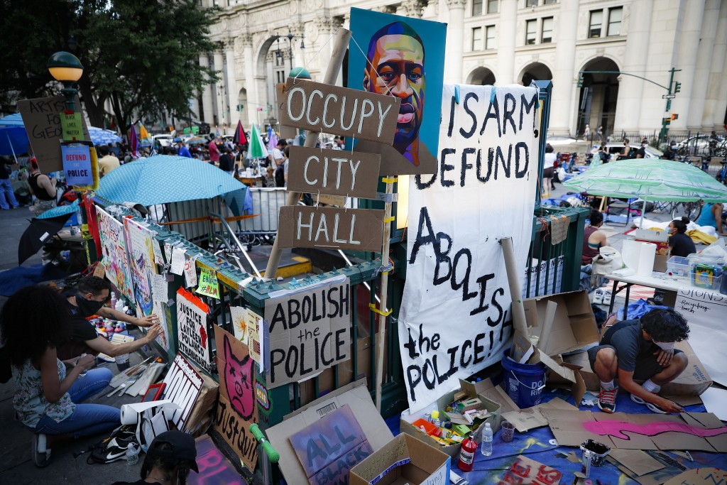 Protesters plaster signs and artwork on a subway entrance as they gather at an encampment outside City Hall, Friday, June 26, 2020, in New York. (AP P...