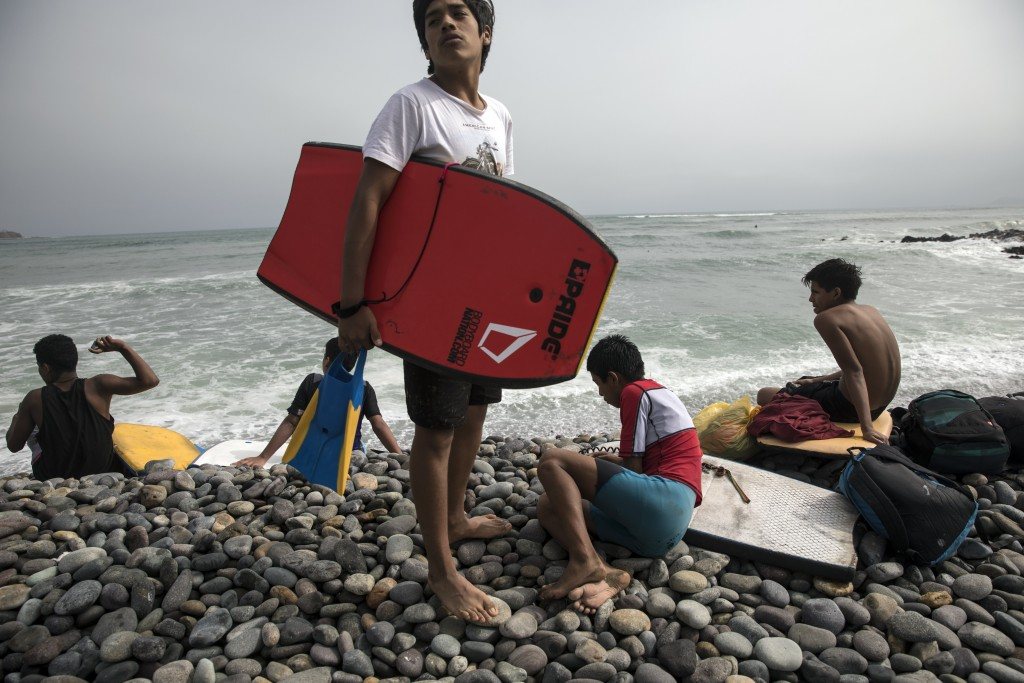 Youth gather before practicing bodyboard in the Pacific Ocean on the coast of Lima, Peru, Friday, June 26, 2020. The emblematic surfers who dot Peru's...